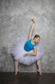 Jovem bailarina dançando balé clássico contra parede rústica