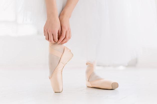 Jovem bailarina dançando, closeup nas pernas e sapatos, em pé na posição de ponta.