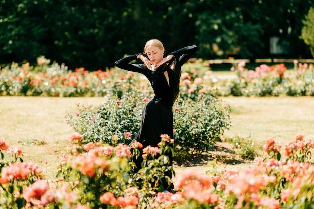 Jovem bailarina de vestido preto, posando e mostrando poses de balé no parque de verão.