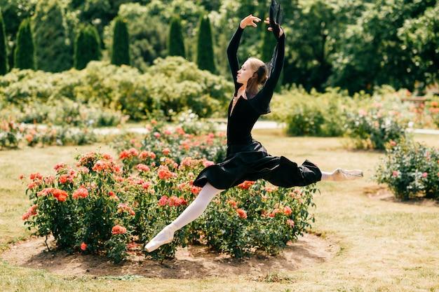 Jovem bailarina de vestido preto pulando entre roseiras no parque