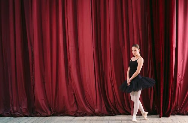Jovem bailarina de vestido preto treina nos bastidores.