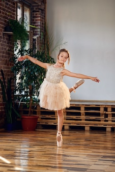 Jovem bailarina em sapatilhas de tutu e ponta praticando movimentos de dança no salão de dança.