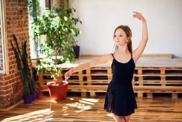 Jovem bailarina em tutu preto praticando movimentos de dança.