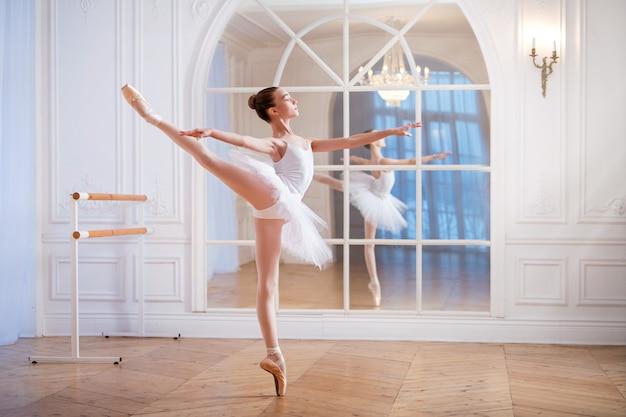 Jovem bailarina em um tutu branco está dançando na ponta em um grande salão bem iluminado em frente a um espelho.