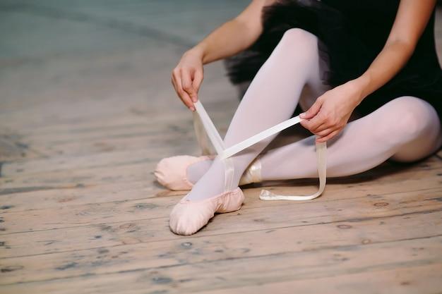 Jovem bailarina em vestido preto treina nos bastidores.