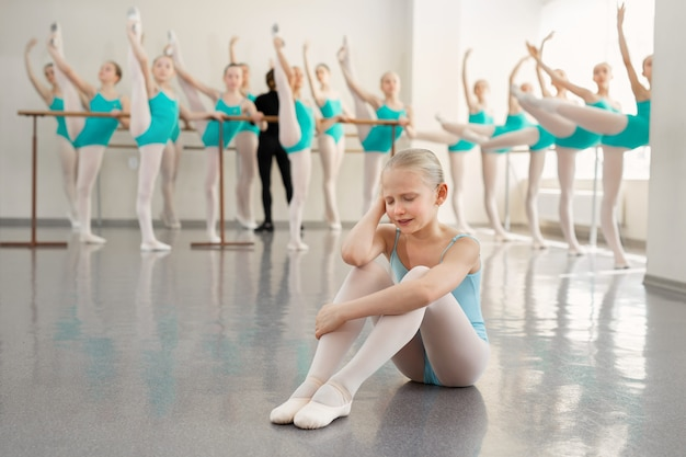 Jovem bailarina está chorando no salão de dança. lágrimas de uma pequena bailarina em uma escola de balé