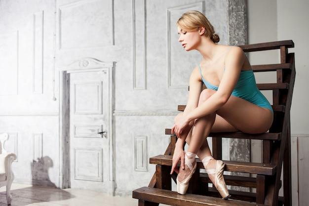 Jovem bailarina feminina amarrar fitas na sua ponta.