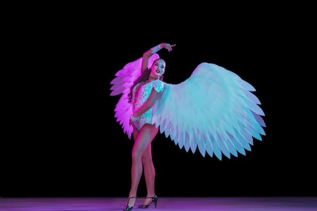 Jovem bailarina feminina com asas de anjo em luz de neon na parede preta