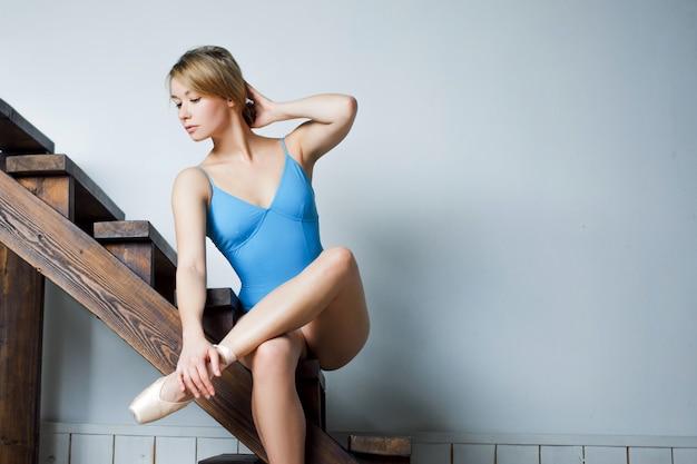 Jovem bailarina feminina de terno azul, sentado na escada