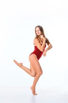 Jovem bailarina linda num vestido bege dançando na parede branca
