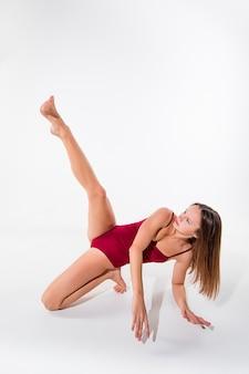 Jovem bailarina linda num vestido bege dançando no fundo branco