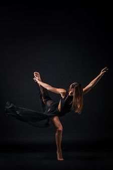 Jovem bailarina linda num vestido bege dançando no fundo preto