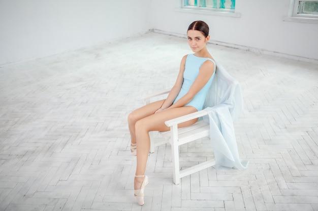Jovem bailarina moderna posando na parede branca