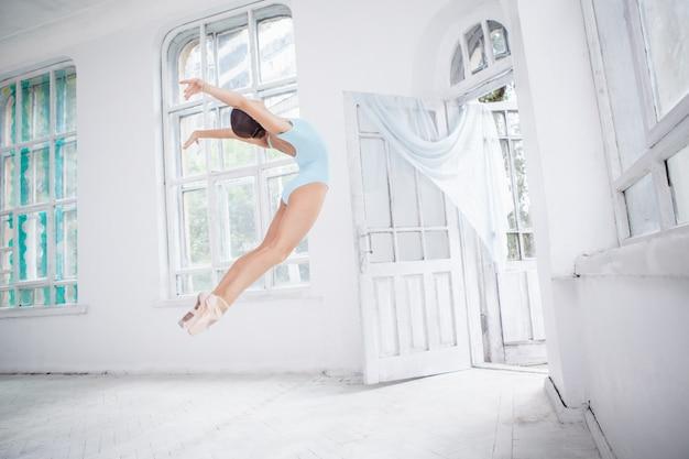 Jovem bailarina moderna pulando na parede branca