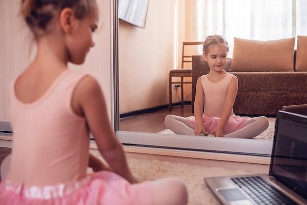 Jovem bailarina praticando coreografia clássica durante aula on-line na escola de balé, auto-isolamento Foto Premium