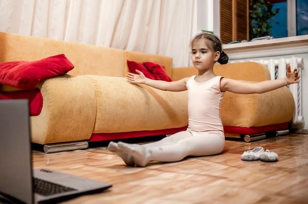 Jovem bailarina praticando coreografia clássica durante aulas online em casa, educação online