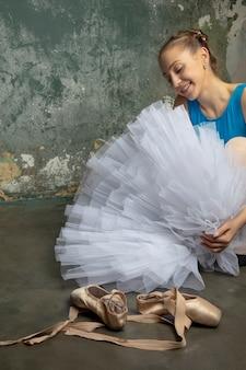 Jovem bailarina sentada no chão junto à parede do grunge