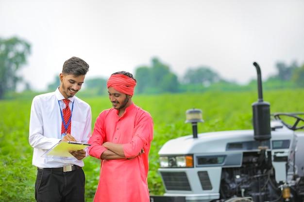 Jovem banqueiro indiano mostrando alguns detalhes para o fazendeiro em papel no campo agrícola
