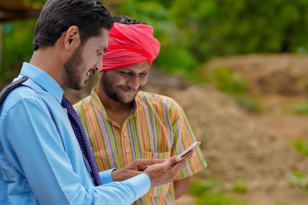 Jovem banqueiro indiano ou agrônomo mostrando alguns detalhes ao fazendeiro no smartphone.