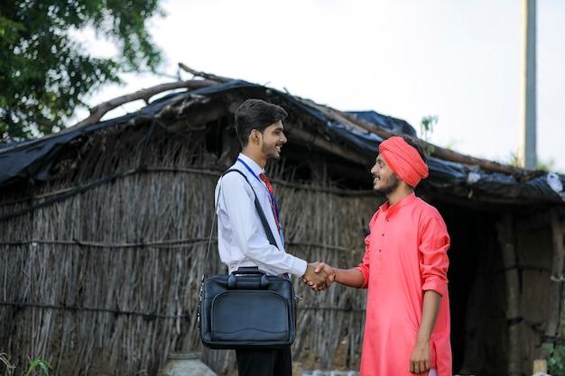 Jovem banqueiro ou agrônomo indiano visita família de agricultores pobres