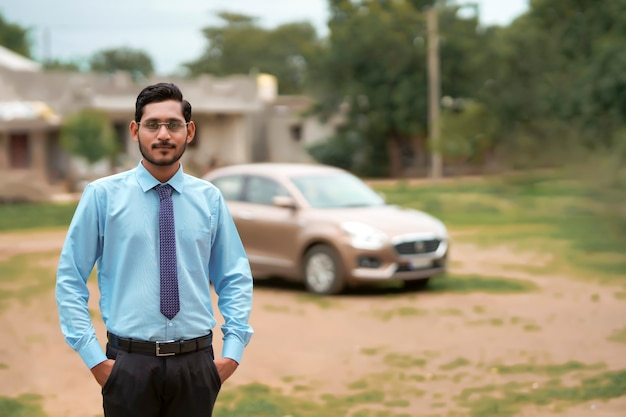 Jovem banqueiro ou financista indiano parado com um carro