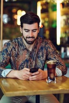 Jovem barba com roupas casuais olhando seu smartphone em um pub moderno