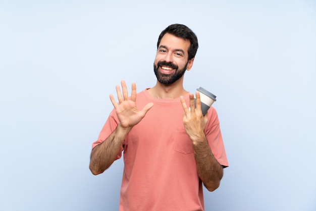 Jovem, barba, segurando, take-away, café, isolado, azul, parede, contagem, oito, dedos