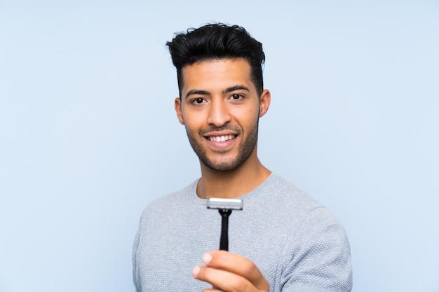 Jovem barbear a barba com expressão feliz