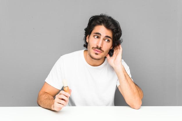 Jovem barbear a barba, tentando ouvir uma fofoca