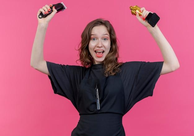 Jovem barbeira alegre vestindo uniforme levantando a tesoura de cabelo e a copa