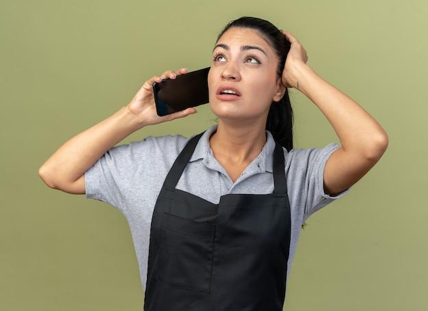Jovem barbeira caucasiana preocupada, vestindo uniforme, falando ao telefone, mantendo a mão na cabeça, olhando para cima, isolada na parede verde oliva
