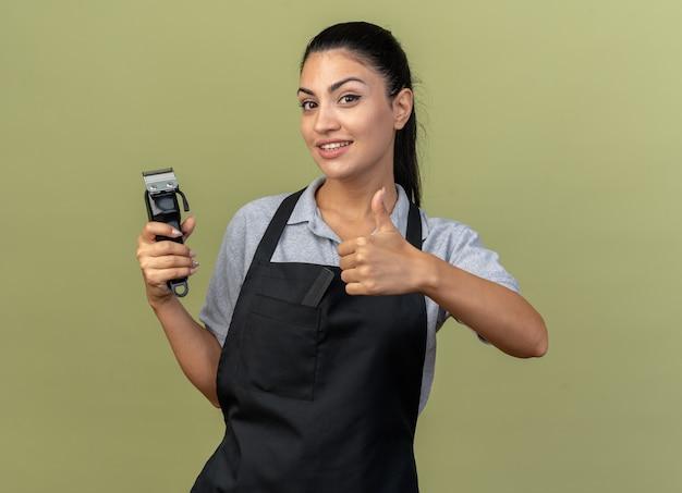 Jovem barbeira caucasiana sorridente, usando uniforme, segurando uma máquina de cortar cabelo, aparecendo o polegar isolado na parede verde oliva