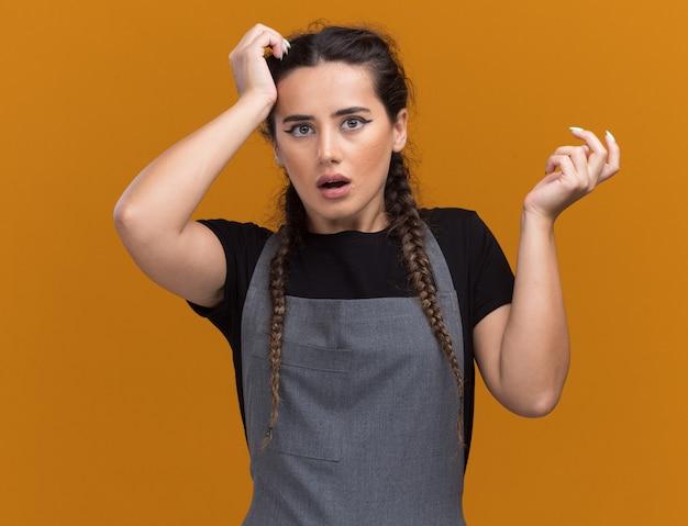 Jovem barbeira confusa de uniforme, segurando a mão na testa, isolada na parede laranja