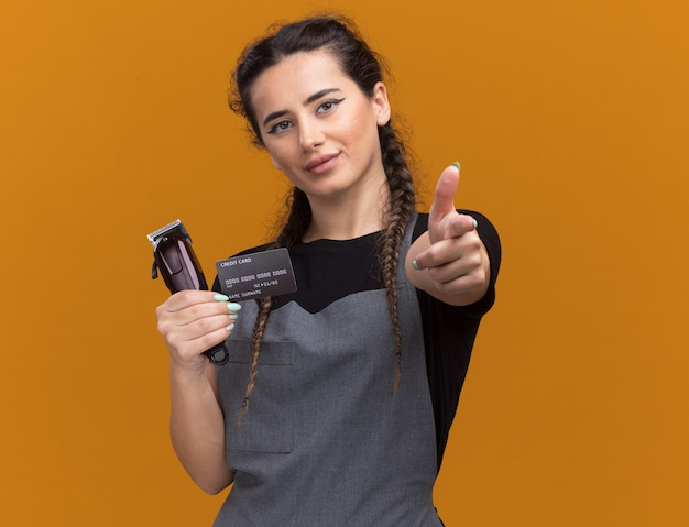 Jovem barbeira de uniforme satisfeita segurando um cartão de crédito e pontos de corte de cabelo isolados na parede laranja