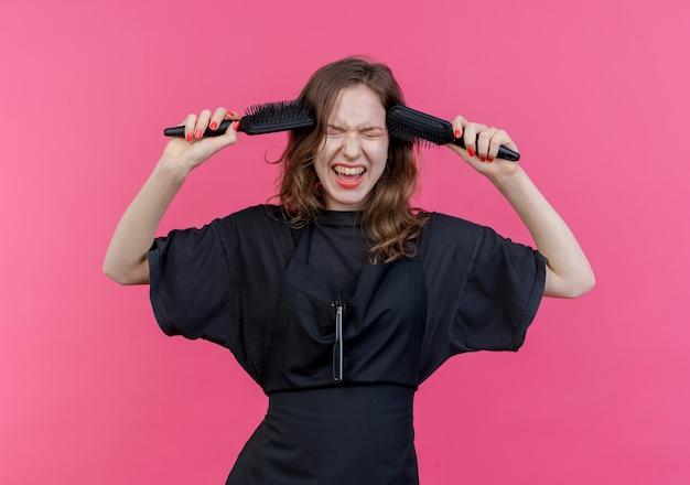Jovem barbeira eslava, estressada, usando uniforme, apontando os pentes para a cabeça com os olhos fechados, isolado no fundo rosa