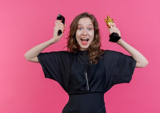 Jovem barbeira eslava impressionada, vestindo uniforme, segurando uma tesoura de cabelo e a taça do vencedor isolada em um fundo rosa