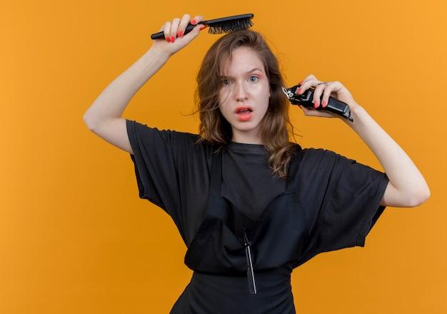Jovem barbeira impressionada vestindo uniforme segurando um pente e uma tesoura de cabelo