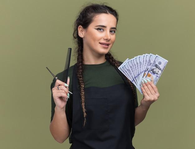 Jovem barbeira satisfeita de uniforme segurando dinheiro com ferramentas de barbeiro isoladas na parede verde oliva
