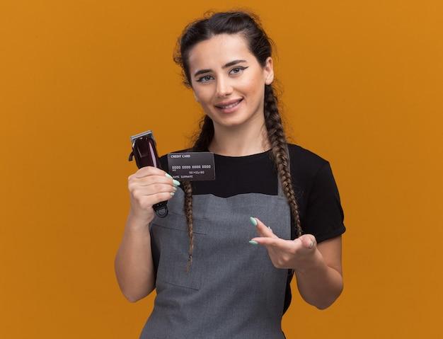 Jovem barbeira sorridente com uniforme segurando e aponta para o cartão de crédito e o cortador de cabelo isolado na parede laranja