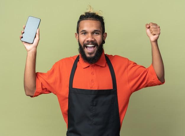 Jovem barbeiro afro-americano alegre vestindo uniforme segurando o telefone celular fazendo gesto de sim isolado na parede verde oliva