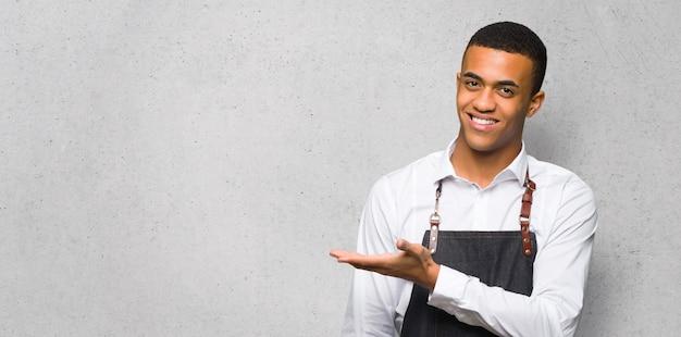Jovem barbeiro afro americano apresentando uma idéia enquanto olha sorrindo para na parede texturizada