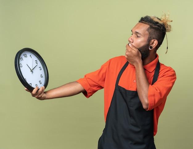 Jovem barbeiro afro-americano preocupado, usando uniforme, segurando e olhando para o relógio, com a mão na boca