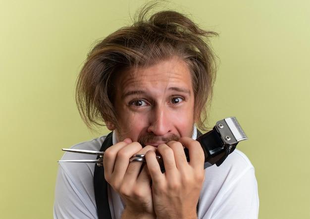 Jovem barbeiro ansioso segurando uma tesoura e uma tesoura de cabelo com cabelo rebelde isolado em verde oliva
