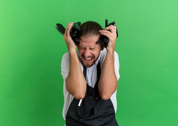 Jovem barbeiro bonito com raiva, usando uniforme, tocando sua cabeça com ferramentas de barbeiro com os olhos fechados, isolado no verde com espaço de cópia