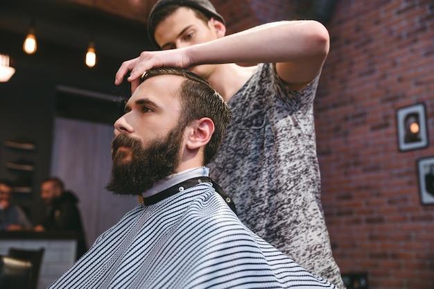 Jovem barbeiro bonito cortando cabelo de jovem atraente hippie barbudo na barbearia