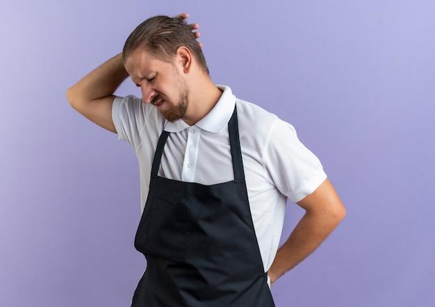 Jovem barbeiro bonito e dolorido vestindo uniforme colocando a mão atrás da cabeça e outra atrás das costas isolada no roxo
