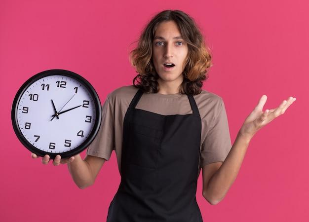 Jovem barbeiro bonito impressionado, vestindo uniforme, segurando o relógio e mostrando a mão vazia