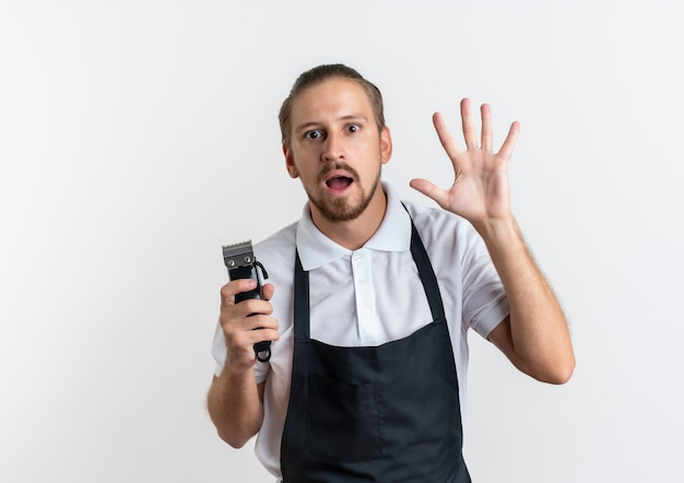 Jovem barbeiro bonito impressionado, vestindo uniforme, segurando uma tesoura de cabelo e mostrando cinco com a mão isolada no branco com espaço de cópia