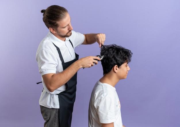 Jovem barbeiro bonito vestindo uniforme em pé em vista de perfil fazendo corte de cabelo para jovem cliente isolado em fundo roxo com espaço de cópia