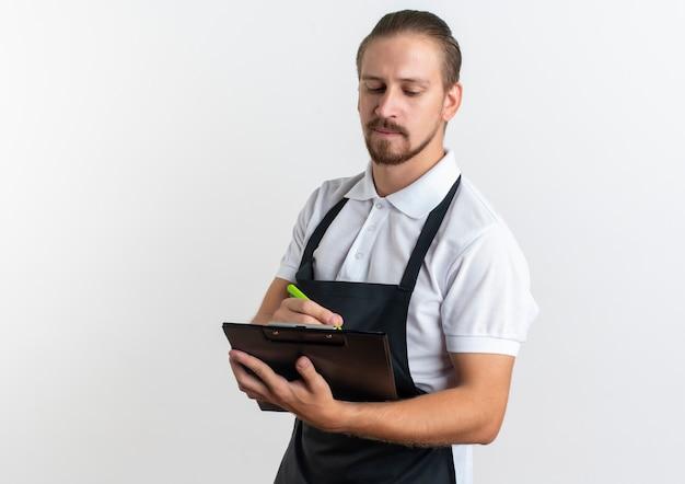 Jovem barbeiro bonito vestindo uniforme segurando uma prancheta e uma caneta olhando para a prancheta isolada no fundo branco com espaço de cópia